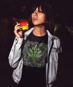 Femme portant un t-shirt Cypress Hill noir avec un motif représentant une feuille de cannabis