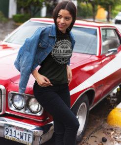 Femme posant près d'une belle voiture portant une veste et un t-shirt Fast and Furious de couleur noire.