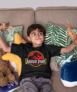 Petit garçon jouant avec des dinosaures et portant un t-shirt Jurassic Park noir