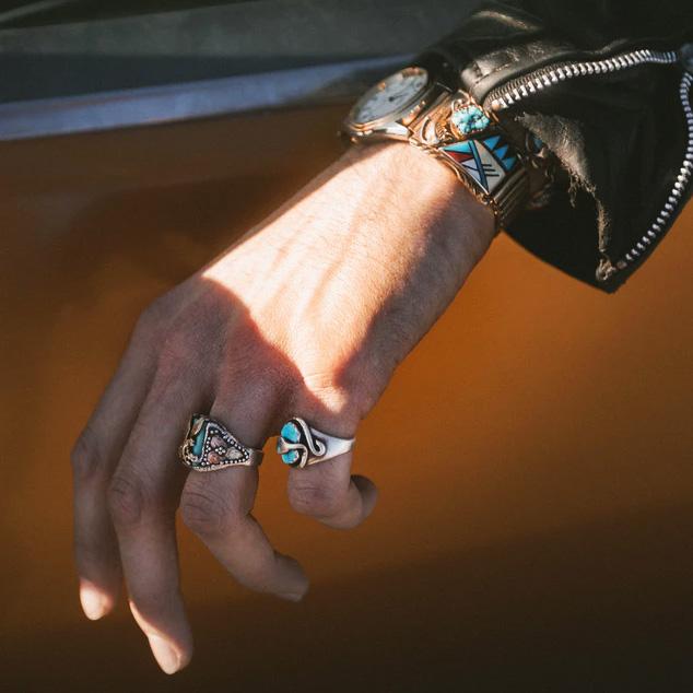 Homme portant des bijoux dont une montre en métal turquoise et des bagues en argent avec des pierres truquoise..
